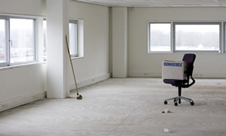 Een afbeelding van een lege ruimte met een bezem en een stoel met daarop een verhuisdoos